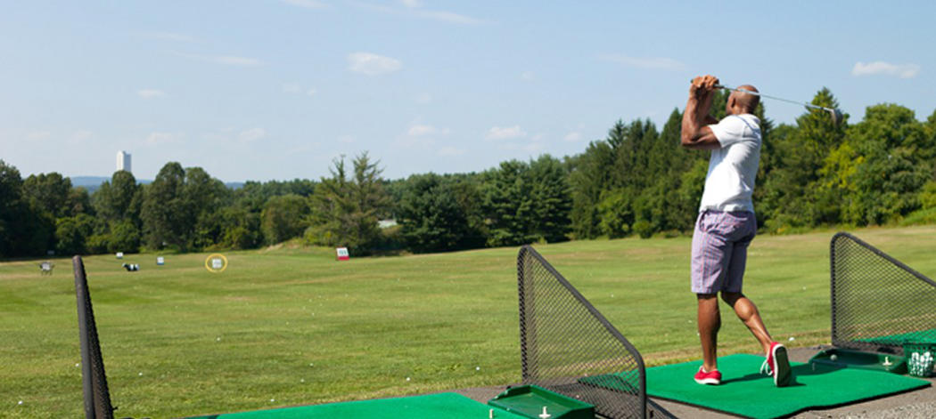 Background image of a male golfer practicing his swing